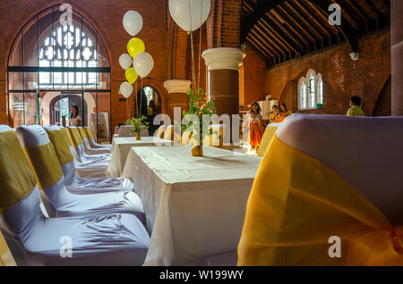 Tables and chairs set out in a church hall, decorated with helium filled balloons and yellow ribbons ready for a party, reception or celebration - Stock Photo