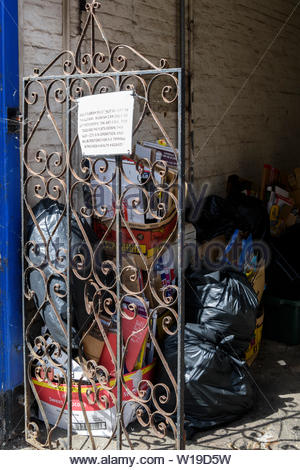 Close up image of black bin bags and rubbish behind an iron gate with a sign attached, Chard, Somerset, England, UK - Stock Photo