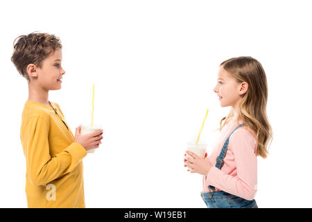 side view of two kids holding milkshakes and looking at each other isolated on white - Stock Photo