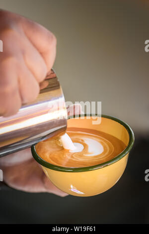 Hands of barista making cappuccino coffee pouring milk on espresso. - Stock Photo