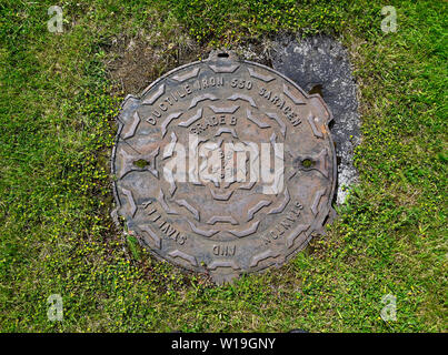 Cast Iron Manhole Cover. Stanton and Stavely. Ductile Iron 550 Saracen. Grade B. BS 469. The House of Bruar, Blair Atholl, Perth and Kinross, Scotland - Stock Photo