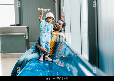 happy african american father looking at son while boy playing with toy plane in airport - Stock Photo