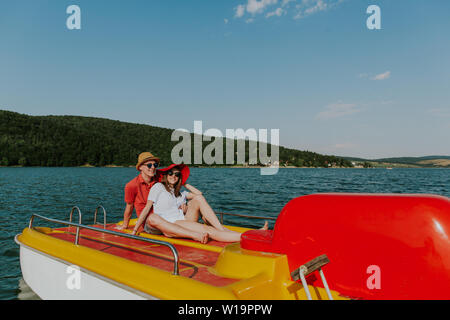Cheerful man and woman having fun boating on the lake. Portrait of couple in love relaxing on pedal boat on warm sunny day. - Stock Photo
