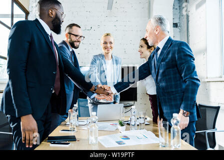 cheerful businesswomen putting hands together with multicultural coworkers - Stock Photo