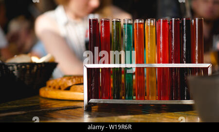 Test tubes with multi-colored liquid. Alcohol in test tubes dark bar. Photo from the bar in Lviv Ukraine - Stock Photo