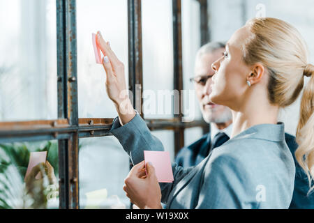 selective focus of attractive blonde woman putting sticky note on window near businessman - Stock Photo