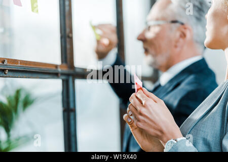 selective focus of businesswoman looking at businessman putting sticky note on window - Stock Photo