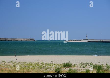Sailing boat exiting the port of Rethimnon, Crete, Greece on a windy day with rough seas. - Stock Photo
