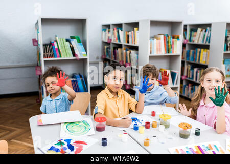 cheerful multicultural kids showing colorful hands with gouache paint