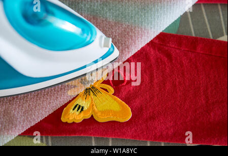 Repairing hole in textile clothing with iron on patches concept. Ironing through cooking paper. - Stock Photo