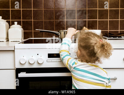 Accident waiting to happen. Toddler girl pulling boiling pot of water over in home kitchen. Hazard at home, skin burn concept( set up, pot is empty). - Stock Photo