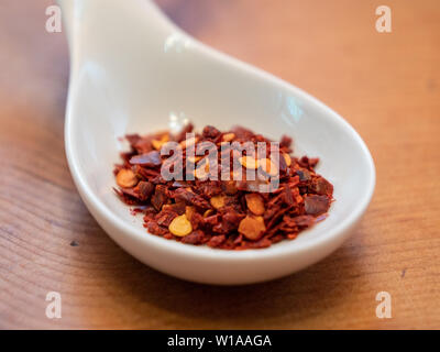 Turkish Red Pepper Flakes in a White Porcelain Spoon on a Wood Table - Stock Photo