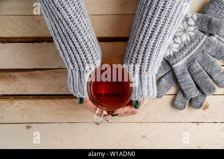 women's hands holding a vintage mug on a wooden background - Stock Photo