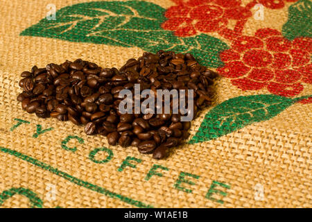 heart shape coffee beans on canvas with picture of coffee plant in the background - Stock Photo