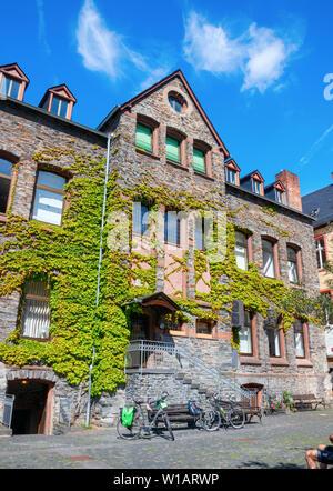BERNKASTEL-KUES, RHINELAND-PALATINATE, GERMANY – MAY 31, 2019: Kues Academy of European intellectual history building overgrown with hedera at the Kar - Stock Photo