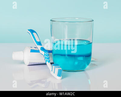 Toothbrush, toothpaste, mouthwash on a white-blue background. The concept of daily dental care, oral hygiene, prevention of diseases of the teeth. - Stock Photo