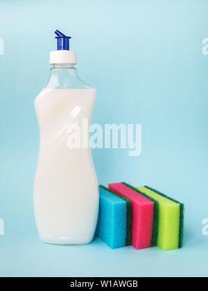 Bottle with white dishwashing liquid and three foam sponges of different colours on a blue background. Kitchen detergent. Household chemicals. - Stock Photo