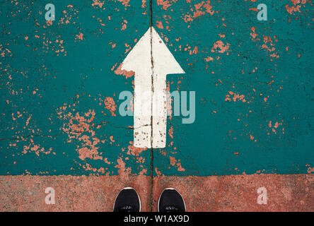 Upward white arrow painted on road. Urban road sign with a person standing on the edge. Colourful grungy texture with a symmetrical crack on asphalt - Stock Photo