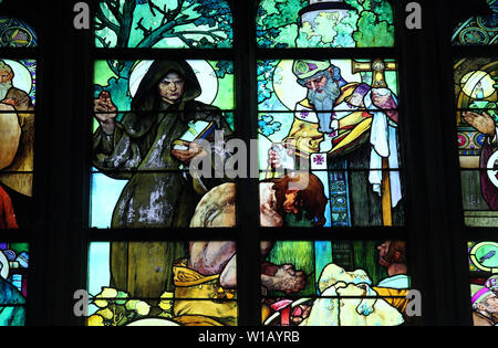 Detail of the stained glass window by Alphonse Mucha at Prague Cathedral showing Saint Cyril and Saint Method performing a baptism - Stock Photo