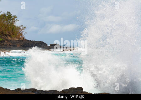 View of waves crashing into the lava rocks to the west of Secret Beach on the Hawaiian Island of Kauai - Stock Photo