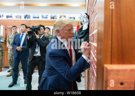 Korean Demilitarized Zone, Korea. 30th June, 2019. President Donald J. Trump signs a brick wall of celebrated visitorÕs autographs Sunday, June 30, 2019, at the Korean Demilitarized Zone. People: President Donald Trump Credit: Storms Media Group/Alamy Live News - Stock Photo