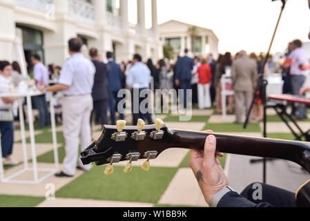 Valencia, Spain - June 20, 2019: Musician playing jazz on guitar contracted to entertain the attendees of a business event. - Stock Photo