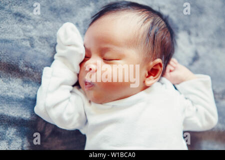 Closeup portrait of cute adorable sleeping Asian Chinese mixed race newborn baby girl boy lying on bed in bedroom. Healthy happy childhood ethnic dive
