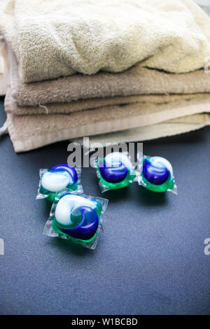 Laundry Day - laundry detergent pods on a laundry folding table with tan towels. - Stock Photo