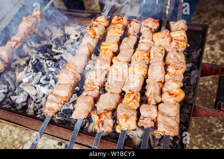 Closeup macro of raw roasted marinated meat barbecue shish kebab shashlik on steel metal skewers lying grill fire brazier with charcoal. - Stock Photo