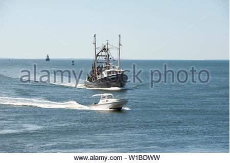New Bedford, Massachusetts, USA - July 1, 2019: Powerboat scoots around clammer Enterprise, hailing port Cape May, New Jersey, as they approach New Be - Stock Photo