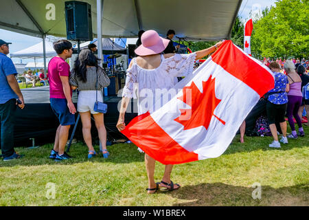 Woman dancing with Canadian flag, Canada Day, North Vancouver, British Columbia, Canada - Stock Photo