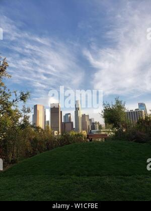 Spectacular view of downtown Los Angeles from a green park with a hill and a bench, Vista Hermosa National Park. - Stock Photo