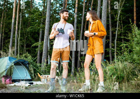 Young couple standing with hot drinks at the camping in the forest, enjoying their summer trip during the sunset - Stock Photo