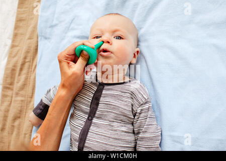 Mother cleaning nose of cute baby - Stock Photo