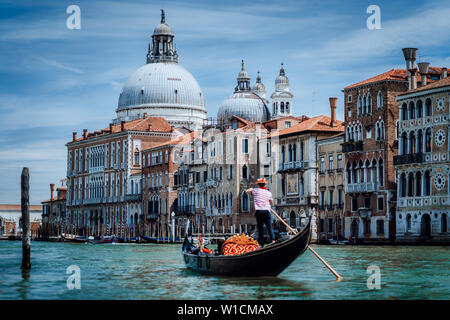 Traditional Gondola and gondolier on Canal Grande with Basilica di Santa Maria della Salute in the background in Venice, Italy. Summer vacation city