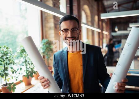 Interior designer smiling. Handsome bearded interior designer smiling after finishing making sketches - Stock Photo