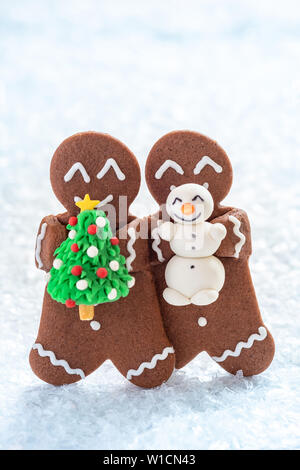 Funny Gingerbread cookie men with tiny marzipan snowman - Stock Photo
