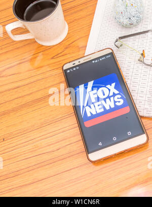 Kolkata, India, February 3, 2019: Fox news app (application) visible on mobile phone screen beautifully placed over a wooden table with a newspaper an - Stock Photo