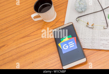 Kolkata, India, February 3, 2019: Google news app (application) visible on mobile phone screen beautifully placed over a wooden table with a newspaper - Stock Photo