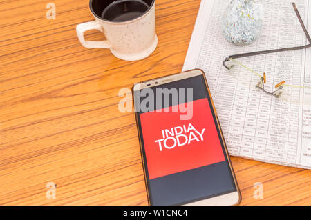 Kolkata, India, February 3, 2019: India Today NEWS app (application) visible on mobile phone screen beautifully placed over a wooden table with newspa - Stock Photo