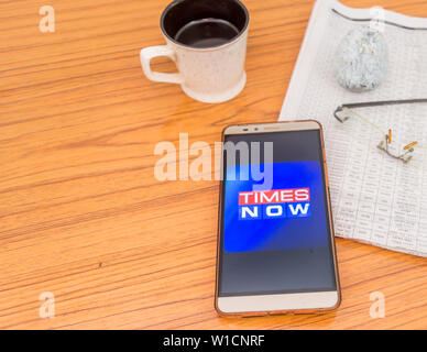 Kolkata, India, February 3, 2019: Times Now news app (application) visible on mobile phone screen beautifully placed over a wooden table with a newspa - Stock Photo