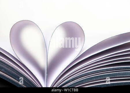 Book pages opened in heart shape isolated on white background. Love of reading, concept of science, learning, romance - Stock Photo