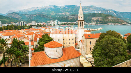 Panorama of the popular resort of Budva, Montenegro, the ancient walls and red-tiled roof, the bay of the Adriatic Sea and the Balkan Mountains. - Stock Photo
