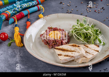 Delicious tartare with toasted bread and salad on a plate on stone background. Healthy lunch meal made of raw meat. Classical French cuisine - Stock Photo