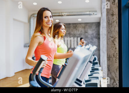 happy women doing cardio workout on bike at gym stock
