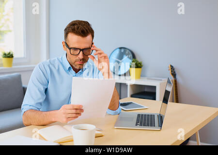 Serious man reading document at home sitting by desk - Stock Photo