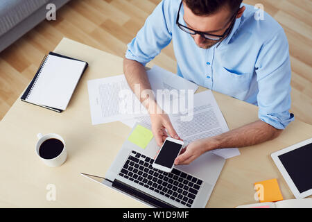 Top view of man using smartphone sitting at  desk with documents and laptop - Stock Photo