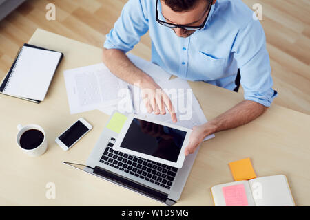 Top view of man using digital tablet sitting at  desk with documents and laptop - Stock Photo