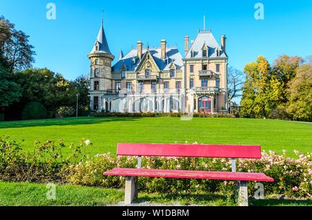 Thun, Switzerland - Oktober 28 2014: Schadau Castle on Thun Lake (Thunersee, Thuner See), red, pink bench - Stock Photo