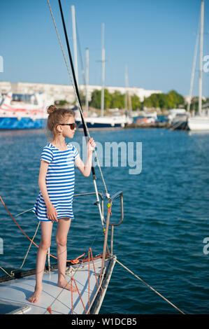 beautiful slim little girl in sunglasses and striped sailor shirt standing on board of white yacht in sea port during summer vacation cruise - Stock Photo